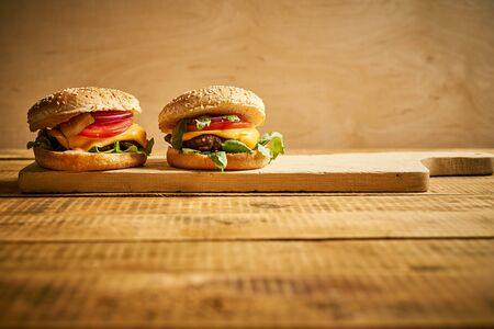 Two tasty burgers on wooden board and black background