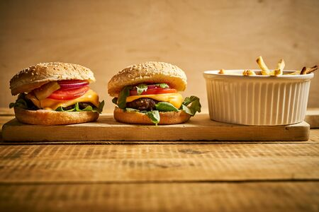 two tasty burgers and fries on wooden board and black background Stock Photo