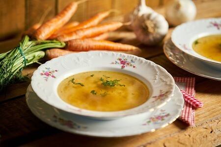 Closeup of delicious home made broth on old wooden table