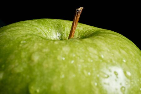 Close up of green organic fresh apple with water drops on black background