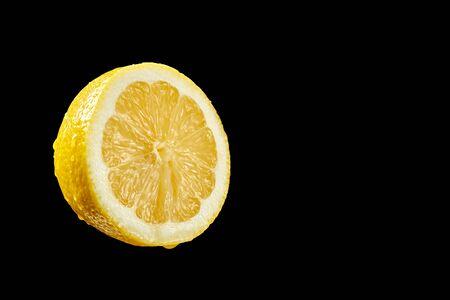 Closeup of fresh yellow organic half lemon with water droplets on black background