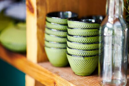 Closeup of bowls on wooden shelf in restaurant prepared for serving