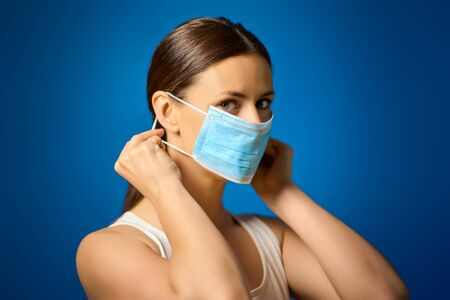 woman in white shirt shows how to wear a mask during a pandemic