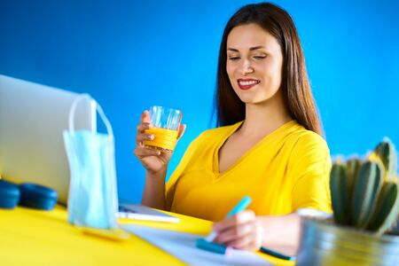 woman drinks juice and works during quarantine Standard-Bild