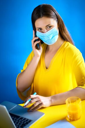 woman in a mask talks on the phone and works during quarantine Standard-Bild