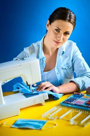 woman sews masks on the machine during quarantine