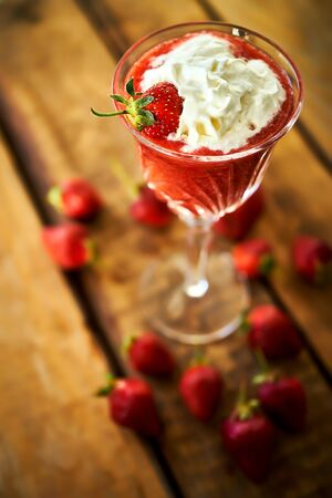 cocktail with fresh strawberries on an old rustic table Standard-Bild