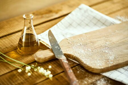 olive oil, knife and cutting board on wooden table