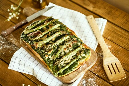 homemade pizza with asparagus and spinach on a rustic wooden table Standard-Bild