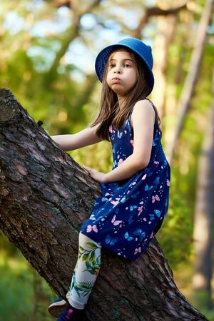 two girls in summer dresses are climbing a tree in the forest