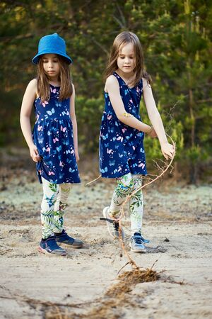 little girls in dresses pull the root on the forest road Standard-Bild - 149207651