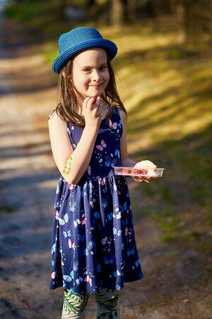 little girl in a blue hat posing in the spring pine forest Standard-Bild - 149207194