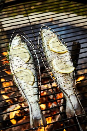 delicious trout with spices roast on a grill over a fire in the summer forest