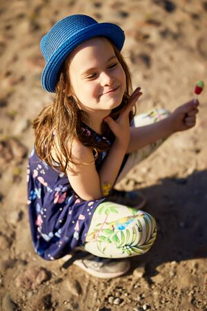 little girl in a blue hat posing in the spring pine forest Standard-Bild - 149208898
