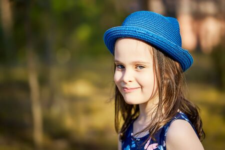 little girl in a blue hat posing in the spring pine forest Standard-Bild - 149152858