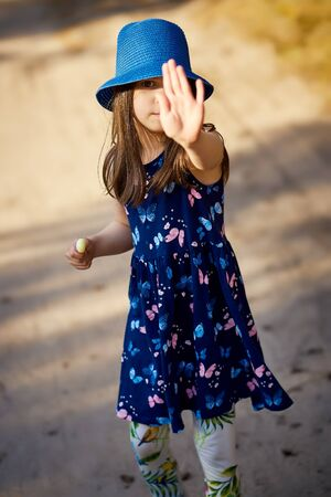 adorable little girl in a blue hat posing in the spring pine forest Standard-Bild