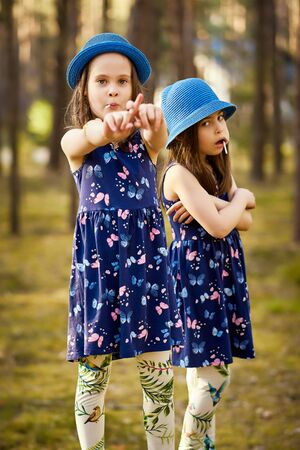 two little girls in blue hats are posing in the spring pine forest Standard-Bild - 149152892
