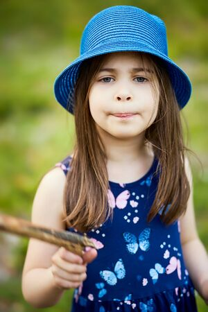 little girl in a blue hat posing in the spring pine forest