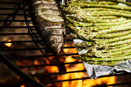 trout with spices and green asparagus roast on a grill over a fire Standard-Bild - 149572336