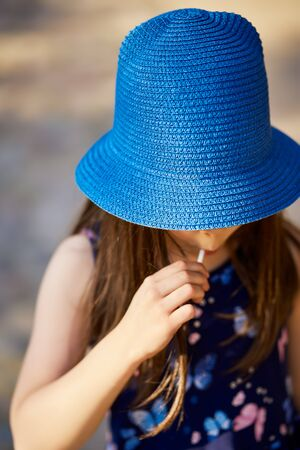 little girl in a blue hat posing in the spring pine forest Standard-Bild - 149154536