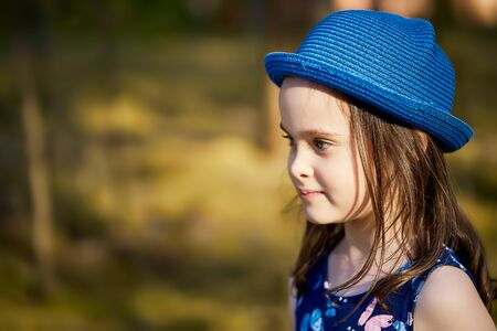 little girl in a blue hat posing in the spring pine forest Standard-Bild - 149156254