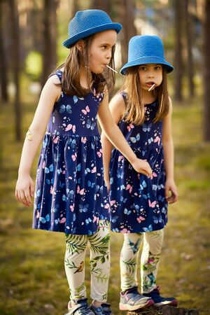two little girls in blue hats are posing in the spring pine forest Standard-Bild - 149212251