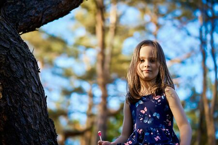 two girls in summer dresses are climbing a tree in the forest Standard-Bild - 149156153