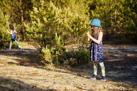 girl in a summer dress runs in a pine forest