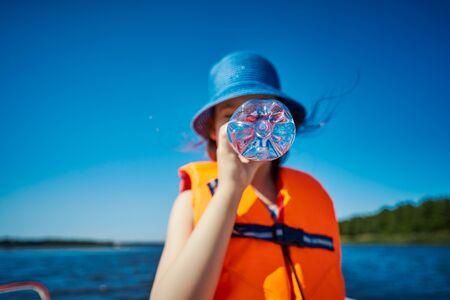 blurry little girl hides her mouth behind a bottle on a motorboat Standard-Bild - 149366097