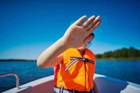 blurry little girl hides her face behind her hand on a motorboat Standard-Bild - 149364414