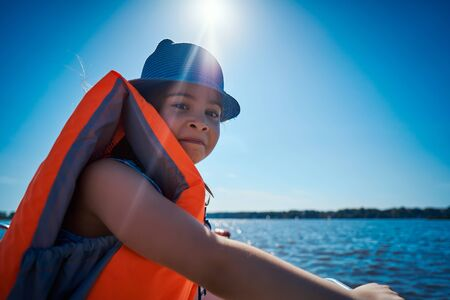 little girl in a swimming vest sits in a motorboat Standard-Bild - 149369734
