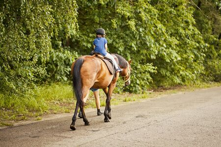 Little girl rides a beautiful horse on the road in the forest Standard-Bild - 149842536
