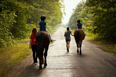 Little girls ride beautiful horses on the road in the forest in summer Standard-Bild - 149918488