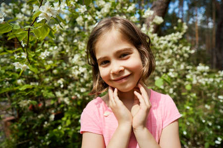 adorable girl making faces with jasmine flower