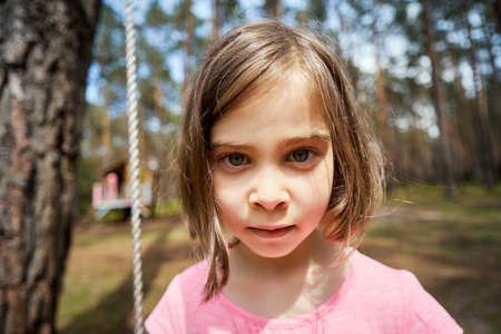 adorable little girl sits on a swing and makes faces Standard-Bild