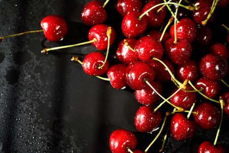 juicy red cherries on a black stone table