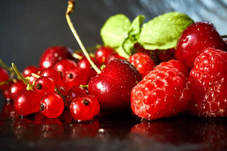 delicious and juicy red raspberries and cherries on a black table Standard-Bild