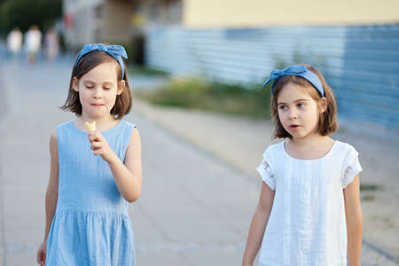 two cute little girls walk around the city and eat ice cream