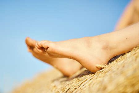 little girls feet in the field of cut rye in summer Banco de Imagens