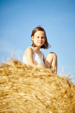 cute little girl sits on mown rye in the field