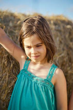 cute little girl sits on mown rye in the field