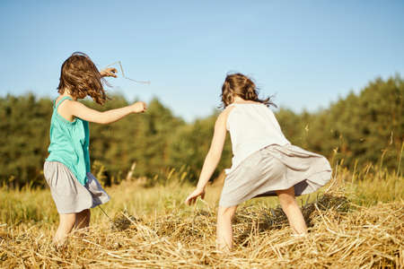 two cute girls are playing with mowed rye in the field Standard-Bild