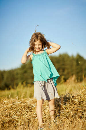 cute little girl is playing in the mown rye field