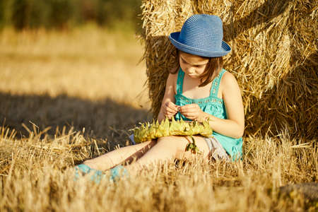 adorable girl eating sunflower seeds on mown rye in the field