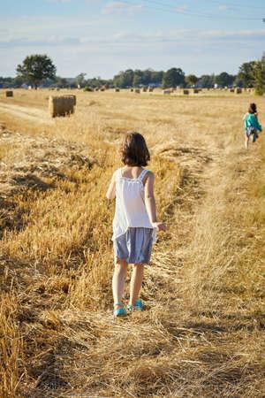 cute little girl walks through the mown rye field