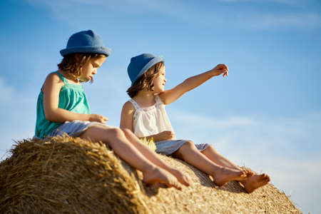 two charming girls are sitting on a roll of mown rye in a field Banco de Imagens - 153312103