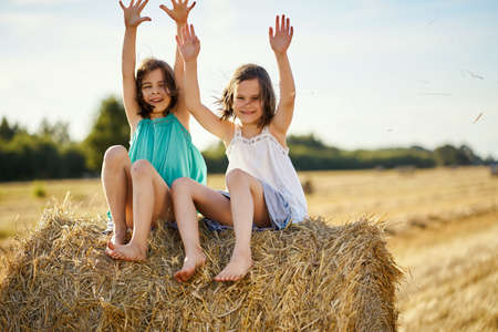 two charming girls are sitting on a roll of mown rye in a field Banco de Imagens - 153312132