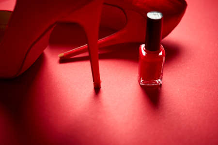 red high heel shoes and nail polish on a minimalist background