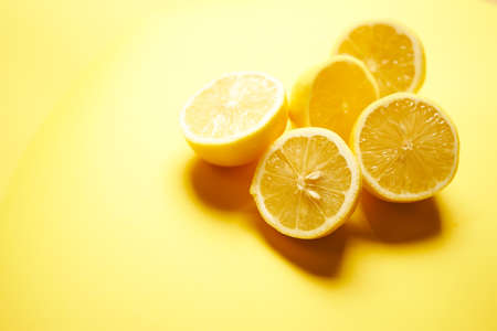 fresh lemons on a yellow minimalistic background Banco de Imagens - 153333360