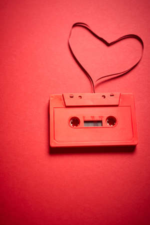 old red cassette tape on a minimalist background